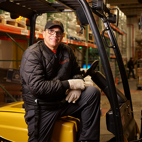 A warehouse employee smiling, sitting on a forklift