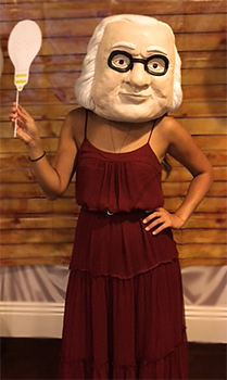 Woman wearing a dress and a giant Benjamin Franklin head
