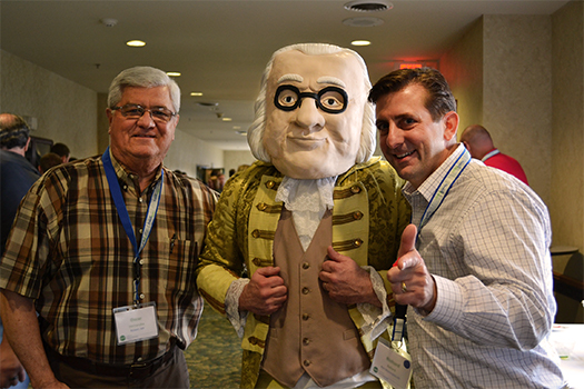 Man dressed in a Benjamin Franklin costume with two men surrounding him