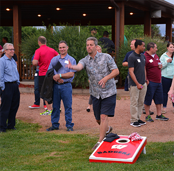 Man at a party playing cornhole