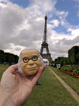 Closeup of a person holding a Benjamin Franklin figure with a blurry Eiffel Tower in the background